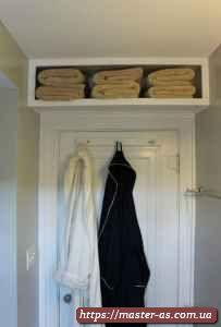 Полка деревянная над дверью в ванной комнате.